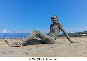Man smeared with healing mud on beach