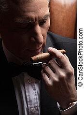 Man smelling a cigar. Close-up of confident mature businessman smelling a cigar