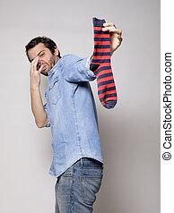 Man smelling a stinky sock