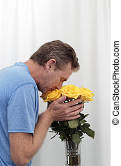 Man Smelling and Holding Yellow Roses Bouquet