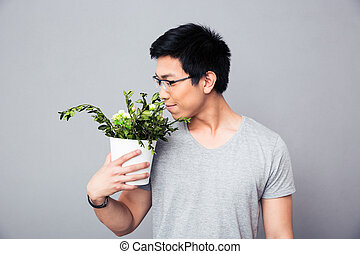 Man smelling flowers in a pot - Asian man smelling flowers...