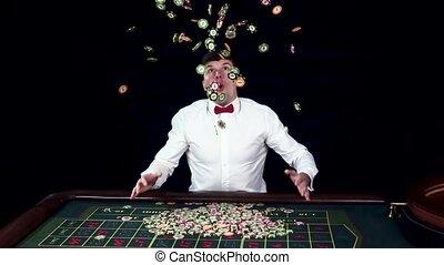 Man smiles hugely as tosses his winnings in the air