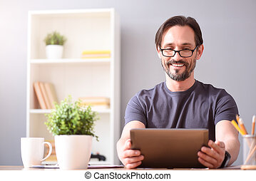 Man smiling and looking at tablet