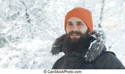 Man smiling and waving at camera outdoors in a winter snowy...