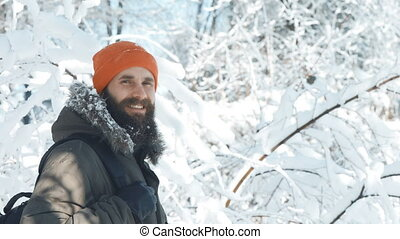Man smiling and waving at camera outdoors in a winter snowy day
