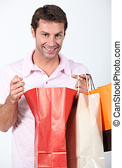 Man smiling holding three shopping bags