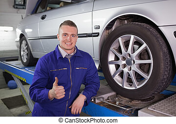 Man smiling next to a car in a garage