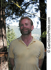 Man Smiling Outdoors - Mature caucasian male with a reserved...
