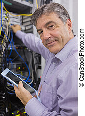 Man smiling while doing server maintenance with tablet in...