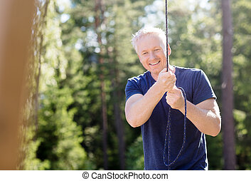 Man Smiling While Holding Rope In Forest