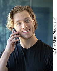 Man smiling while talking on cell phone