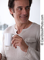 Man smiling with a cup of tea.