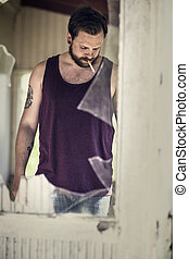 Man smoke cigarette behind broken window