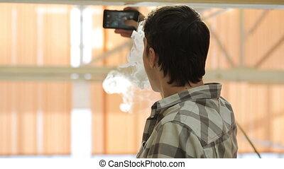 Man smoke vaporizer and take selfie. Thick cloud of vapor