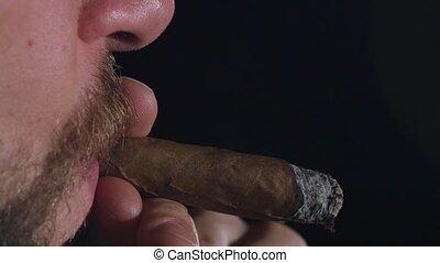 Man Smokes a Cigar. Takes a big drag and puffs smoke. Black....