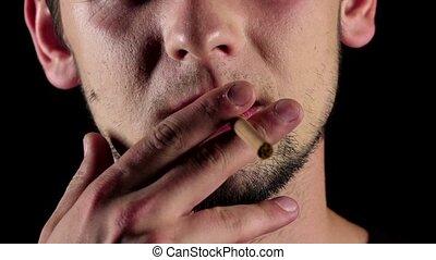 Man smokes a cigarette. Bad habits. Black. Close up. Slow motion