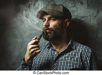 man smokes a pipe standing near the wall.