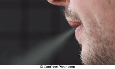Man smokes a roll-up cigarette.
