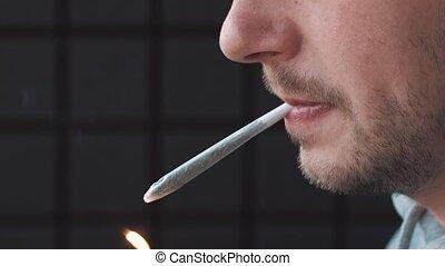 Man smokes a roll-up Marijuana.