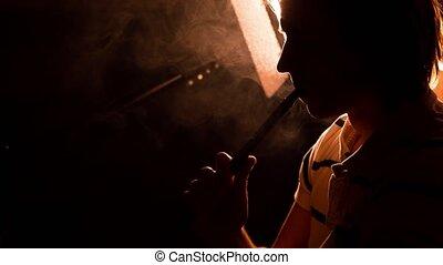 Man smokes hookah one - A man smokes a hookah a close-up