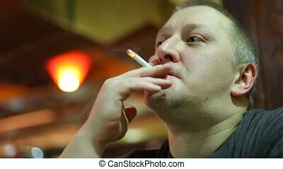 Man smokes. Indoor.
