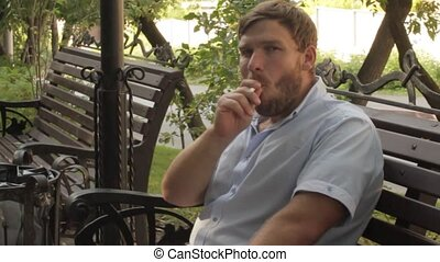 man smokes on the bench in the park