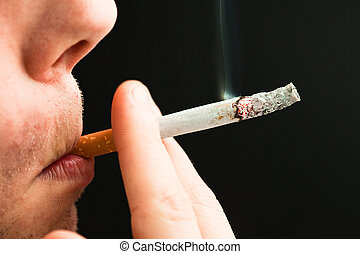 Man smoking a cigarette against a black background
