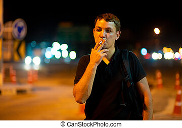 man smoking a cigarette on the street at night.