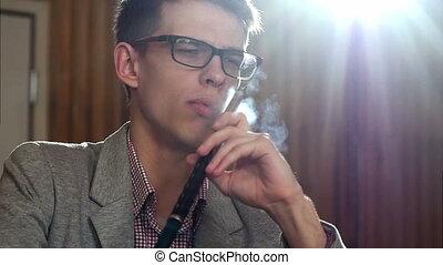 Man smoking a hookah and coughing