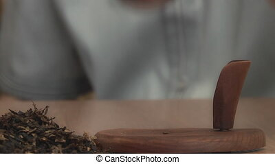 man smoking a pipe with tobacco