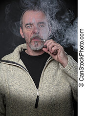 Man smoking an e-cigarette with black background