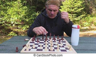 Man smoking and playing chess