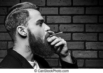 Man smoking. Black and white portrait of handsome young bearded man smoking a cigarette while standing against brick wall