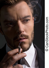 Man smoking. Bossy young man in formal wear smoking while standing isolated on black