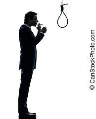 man smoking cigarette in front of hangman noose silhouette -...