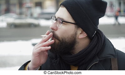 Man smoking cigarette intensively outdoors, nervous scene