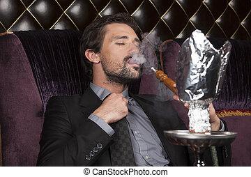 man smoking hookah at arabic restaurant. young man smoking...