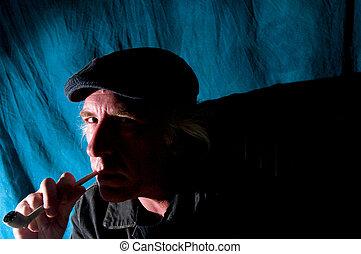 man smoking pipe in dark