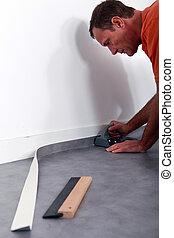 Man smoothing linoleum floor
