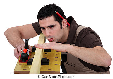Man smoothing plank of wood with plane