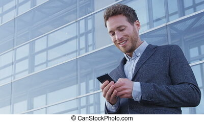 Man sms texting using app on smart phone in city business ...