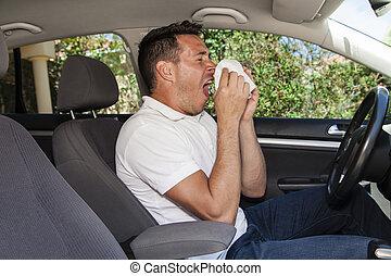 Man allergic to pollen sneezing into hankie inside a car