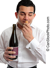 Man sniffing wine cork