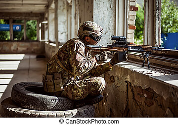 Man sniper with automatic rifle with a telescopic sight