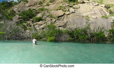 Man snorkeling in a hip deep turquoise water - A wide shot...