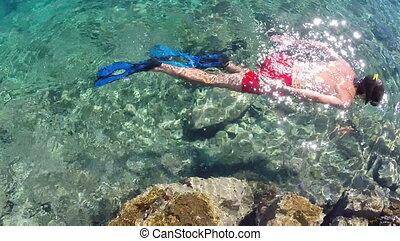 Man snorkeling in turquoise sea water