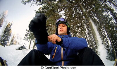 Man snowboarder wears gloves and a mask