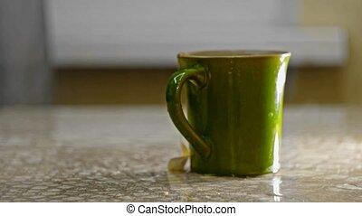 Man soak up the split liquid with a cloth around tea cup on...