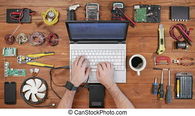 Man software engineer working with a laptop and an external hard drive. Wooden table top view. Download files and disconnects the wire