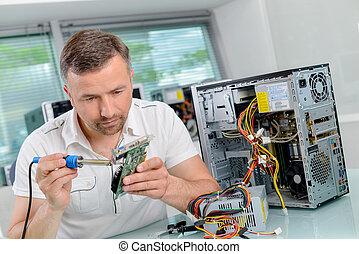 Man soldering computer component